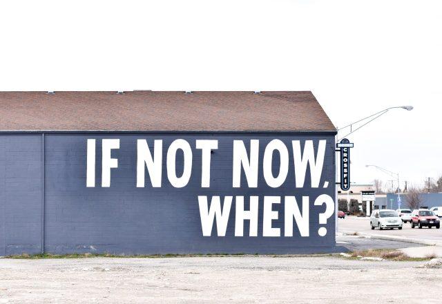 """blaues Gebäude mit """"wenn nicht jetzt, wann?""""  seitlich gemalt"""