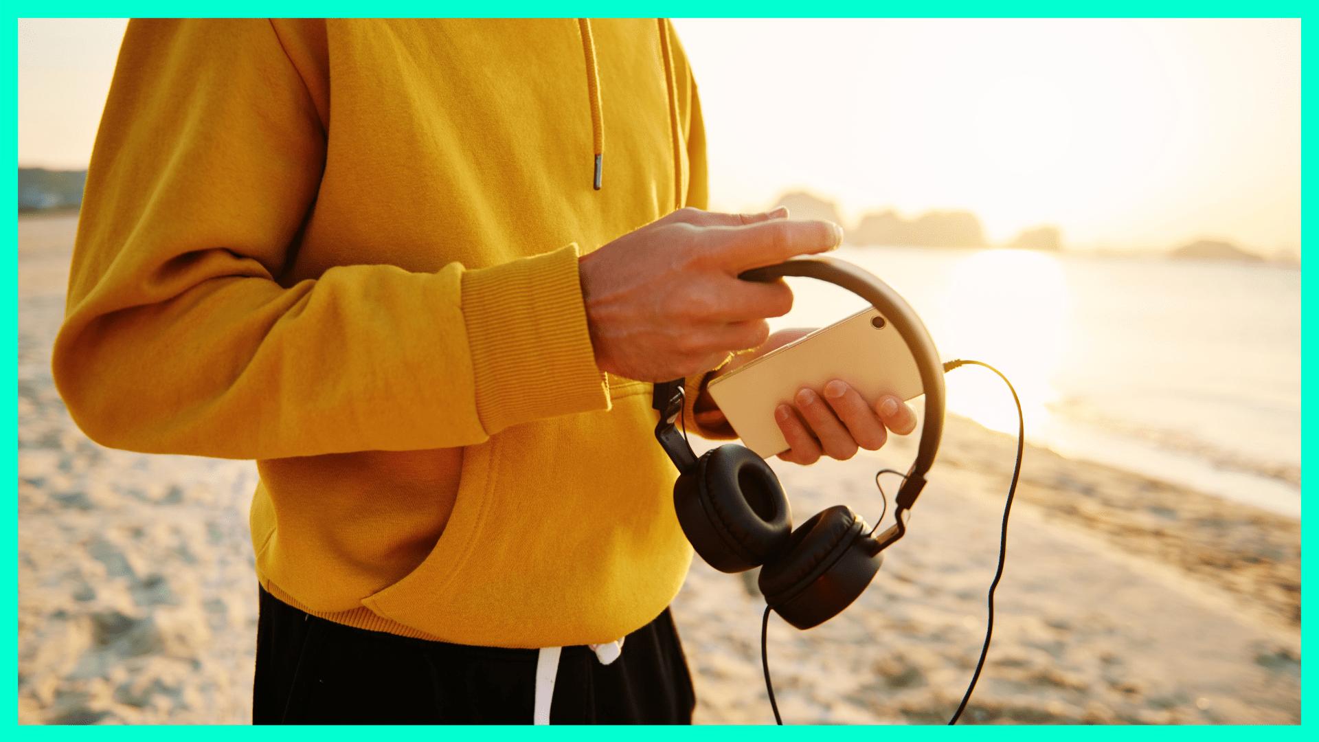 Person mit Kopfhörern und einem iPhone