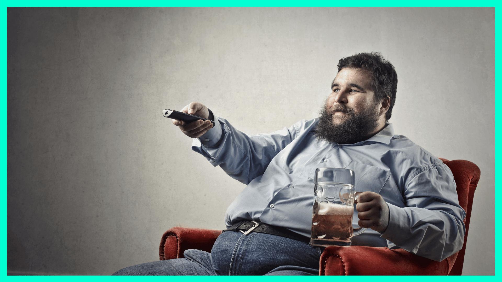 Mann sitzt auf der Couch mit Bier und TV-Fernbedienung